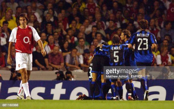 Inter Milan's Andy van der Meyde celebrates with teammates after scoring the second goal as Arsenal's Robert Pires walks away dejected