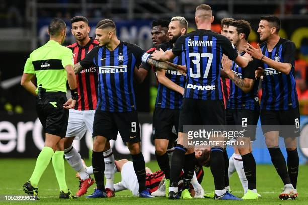 Inter Milan's Argentine forward and team captain Mauro Icardi prevents his teammates to argue with referee Marco Guida after AC Milan's Argentine...