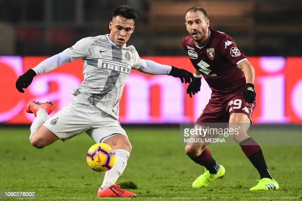 Inter Milan's Argentine forward Lautaro Martinez kicks the ball despite Torino's Italian defender Lorenzo De Silvestri during the Italian Serie A...