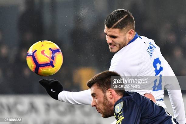 Inter Milan's Argentine forward Mauro Icardi and Chievo's Italian defender Mattia Bani go for a header during the Italian Serie A Football match...