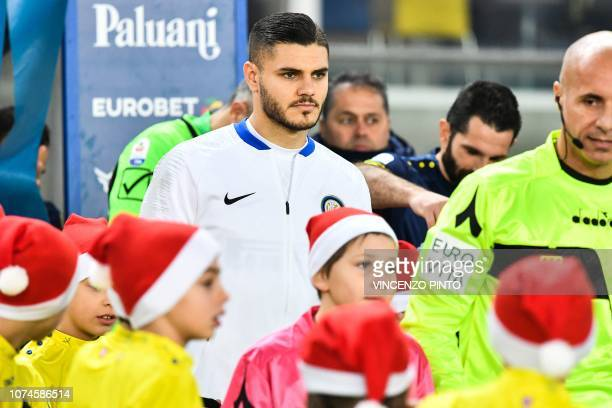 Inter Milan's Argentine forward Mauro Icardi prepares to enter the pitch with children wearing Santa Claus Christmas hoods prior to the Italian Serie...
