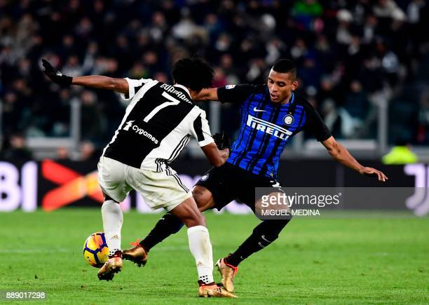 Inter Milan's Brazilian defender Henrique Dalbert fights for the ball with Juventus' Colombian forward Juan Cuadrado during the Italian Serie A...