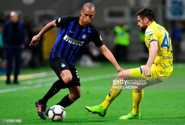 Inter Milan's Brazilian defender Joao Miranda vies with Chievo's Serbian defender Nenad Tomovic during the Italian Serie A football match between...