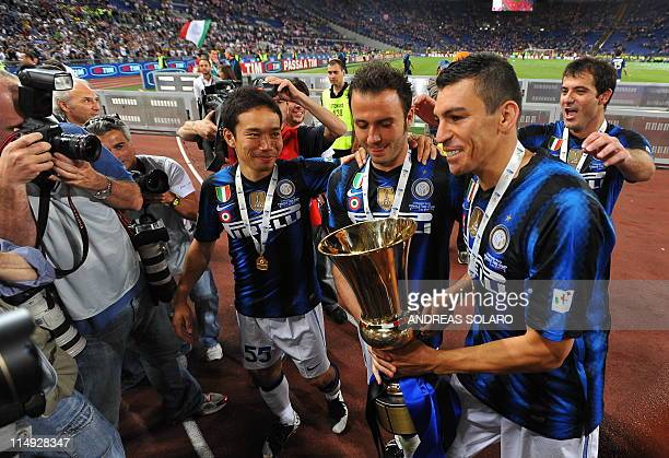 Inter Milan's Brazilian defender Lucio holds the trophy next to his teammates Pazzini and Nagatomo as he celebrates at the end of the match against...