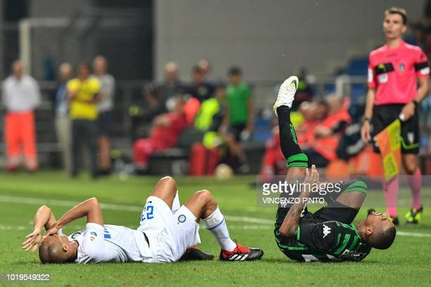 Inter Milan's Brazilian defender Miranda and Sassuolo's Ghanaian forward Kevin-Prince Boateng react in pain after colliding during the Italian Serie...