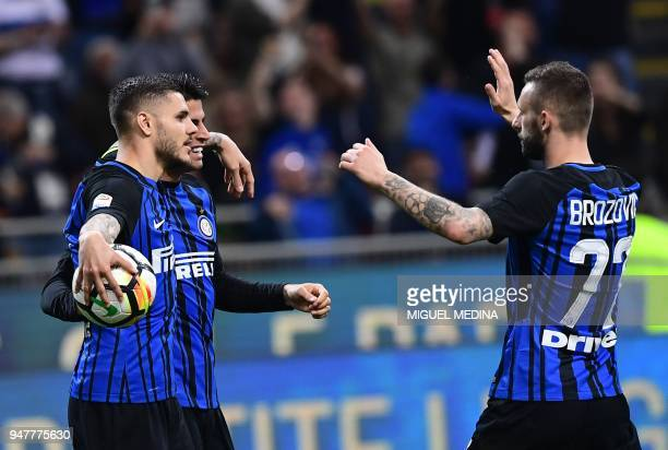 Inter Milan's captain Argentinian forward Mauro Icardi celebrates with teammates Portuguese forward Joao Cancelo and Croatian midfielder Marcelo...