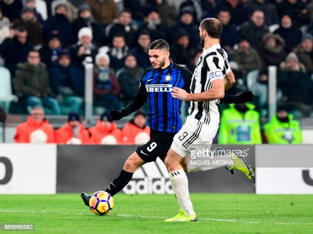 Inter Milan's captain Argentinian forward Mauro Icardi fights for the ball with Juventus' Italian defender Giorgio Chiellini during the Italian Serie...