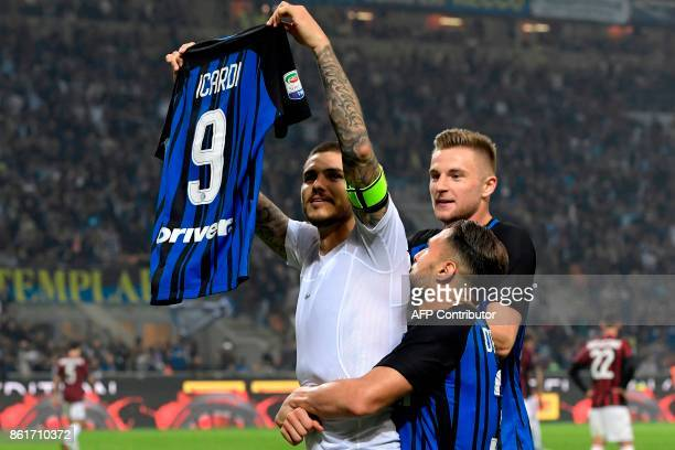Inter Milan's Captain Argentinian forward Mauro Icardi shows his jersey to supporters as he celebrates with teammates at the end of the Italian Serie...
