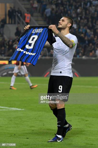 Inter Milan's Captain Argentinian forward Mauro Icardi shows his jersey to supporters as he celebrates at the end of the Italian Serie A football...