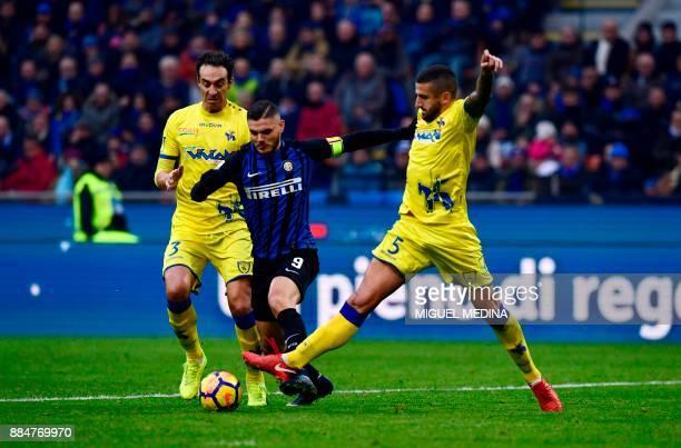 Inter Milan's Captain, Argentinian forward Mauro Icardi vies with Chievo's Italian defender Dario Dainelli and Chievo's Italian defender Alessandro...