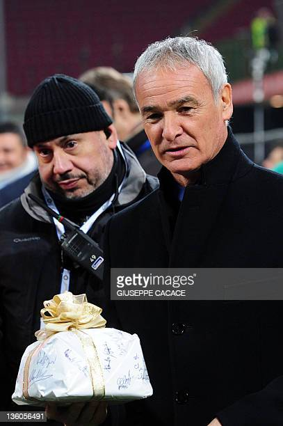 Inter Milan's coach Claudio Ranieri holds a panettone he received as present before the Italian Serie A football match between Inter Milan and Lecce...