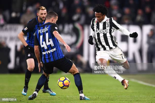 Inter Milan's Croatian forward Ivan Perisic fights for the ball with Juventus' Colombia midfielder Juan Cuadrado during the Italian Serie A football...
