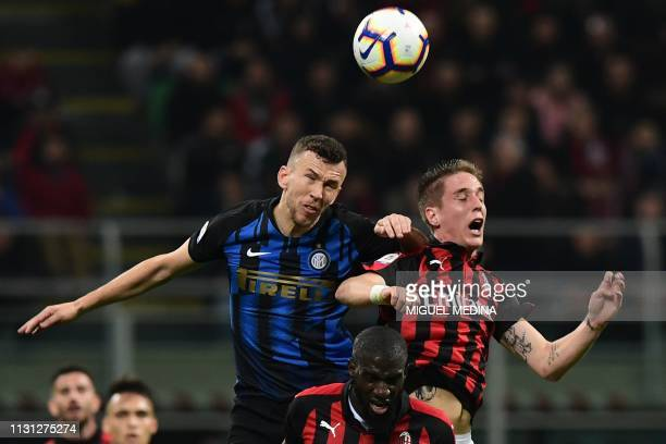 Inter Milan's Croatian midfielder Ivan Perisic and AC Milan's Italian defender Andrea Conti go for a header during the Italian Serie A football match...