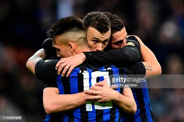 Inter Milan's Croatian midfielder Ivan Perisic is congratulated by teammates Inter Milan's Argentinian forward Lautaro Martinez and Inter Milan's...