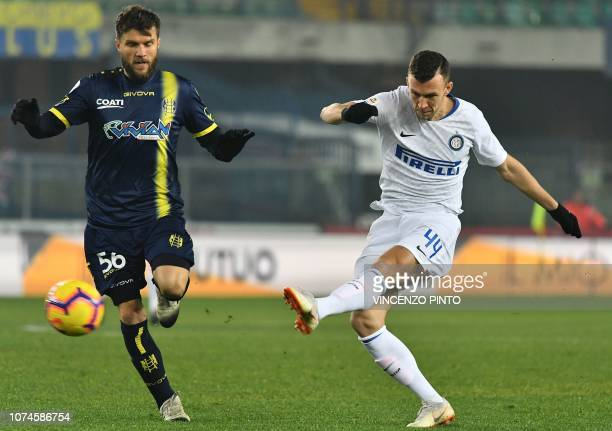 Inter Milan's Croatian midfielder Ivan Perisic kicks the ball past Chievo's Finnish midfielder Perparim Hetemaj during the Italian Serie A Football...