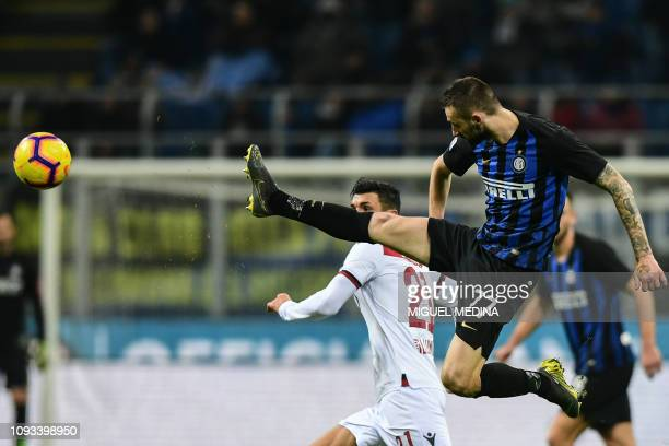 Inter Milan's Croatian midfielder Marcelo Brozovic goes airborne as he clears a ball under pressure from Bologna's Italian midfielder Roberto Soriano...