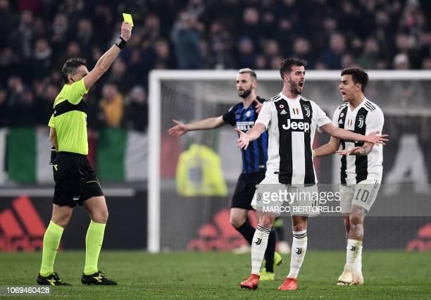 Inter Milan's Croatian midfielder Marcelo Brozovic receives a yellow card as Juventus' Argentine forward Paulo Dybala and Juventus' Bosnian...