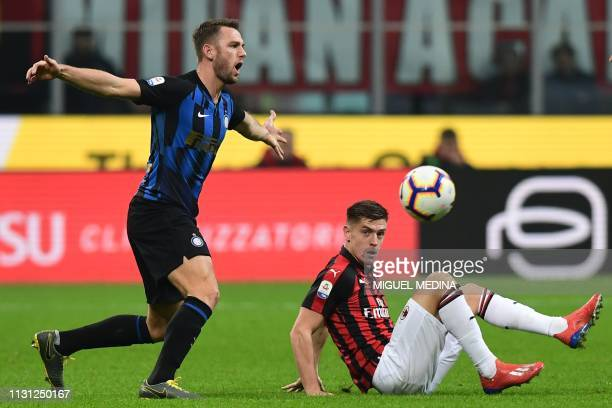 Inter Milan's Dutch defender Stefan de Vrij and AC Milan's Polish forward Krzysztof Piatek go for the ball during the Italian Serie A football match...