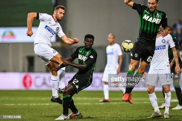 Inter Milan's Dutch defender Stefan de Vrij shoots on goal despite Sassuolo's Ghanaian midfielder Alfred Duncan and Sassuolo's Brazilian defender...