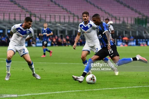 Inter Milan's English midfielder Ashley Young centres the ball despite Brescia's Italian midfielder Stefano Sabelli and Brescia's Italian midfielder...
