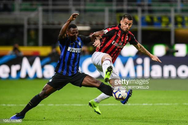 Inter Milan's Ghanaian midfielder Kwadwo Asamoah and AC Milan's Spanish forward Suso go for the ball during the Italian Serie A football match Inter...