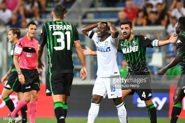 Inter Milan's Ghanaian midfielder Kwadwo Asamoah and Sassuolo's midfielder Francesco Magnanelli react during the Italian Serie A football match...