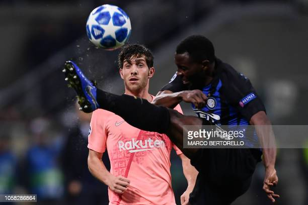 Inter Milan's Ghanaian midfielder Kwadwo Asamoah clears the ball under pressure from Barcelona's Spanish midfielder Sergi Roberto during the UEFA...