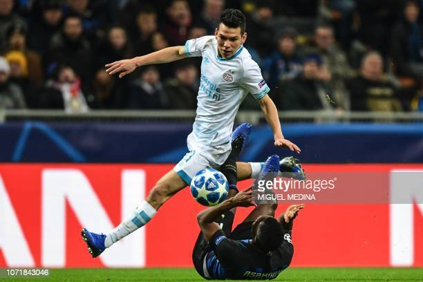 Inter Milan's Ghanaian midfielder Kwadwo Asamoah falls while challenging PSV Eindhoven's Mexican forward Hirving Lozano during the UEFA Champions...