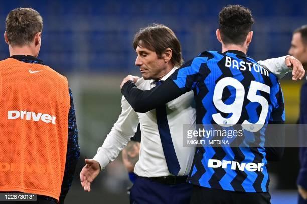 Inter Milan's Italian coach Antonio Conte embraces Inter Milan's Italian defender Alessandro Bastoni at the end of the Italian Serie A football match...