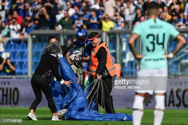 Inter Milan's Italian defender Cristiano Biraghi looks on as security staffers evacuate a parachutist that unexpectedly landed on the pitch during...