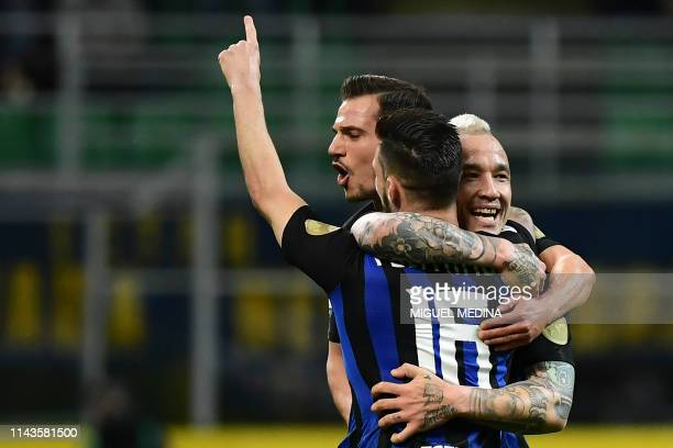 Inter Milan's Italian forward Matteo Politano is congratulated after scoring a goal by teammates Inter Milan's Belgium midfielder Radja Nainggolan...