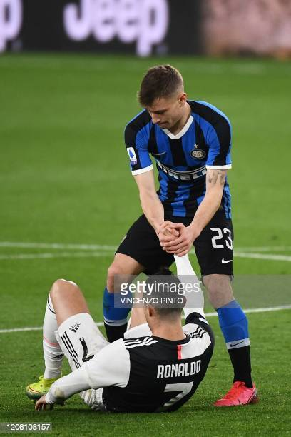 Inter Milan's Italian midfielder Nicolo Barella helps Juventus' Portuguese forward Cristiano Ronaldo to stand up during the Italian Serie A football...