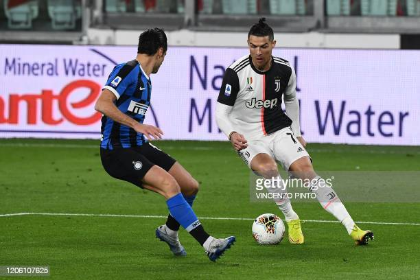 Inter Milan's Italian midfielder Nicolo Barella vies with Juventus' Portuguese forward Cristiano Ronaldo during the Italian Serie A football match...