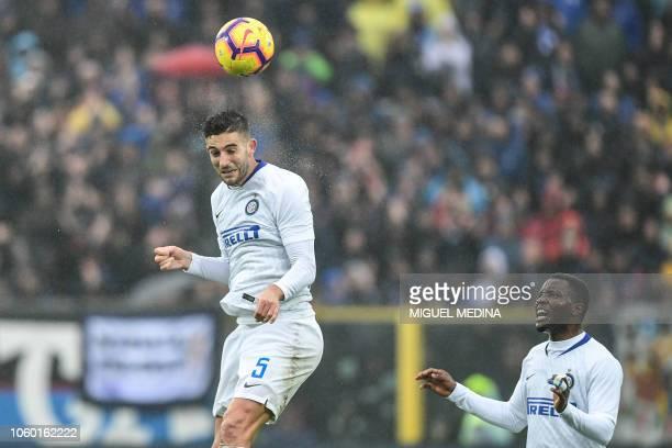 Inter Milan's Italian midfielder Roberto Gagliardini heads the ball as Inter Milan's Ghanaian midfielder Kwadwo Asamoah looks on during the Italian...
