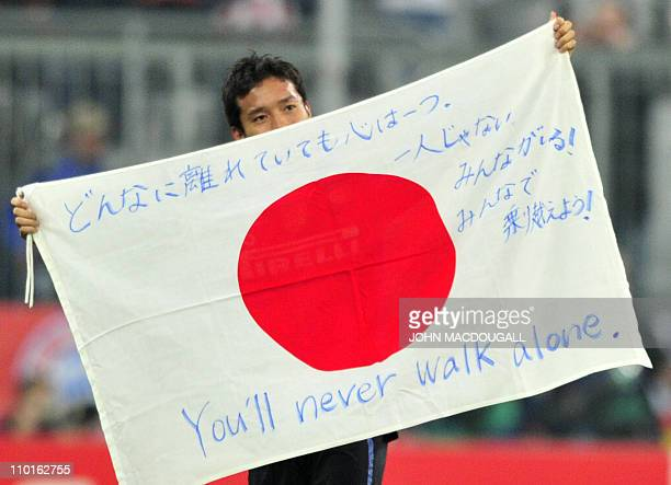 Inter Milan's Japanese defender Yuto Nagatomo displays a Japanese flag bearing the inscription 'You'll never walk alone' in support of Japan's...
