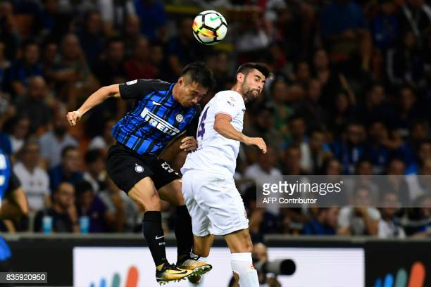 Inter Milan's Japanese defender Yuto Nagatomo jumps for the ball with Fiorentina's Italian midfielder Marco Benassi during the Italian Serie A...