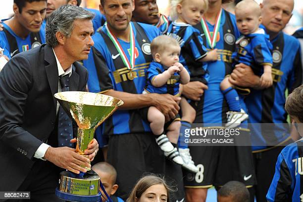 Inter Milan's Portuguese coach Jose Mourinho holds the trophy to celebrate the 17th Italian serie A football championship 'scudetto'at the end of the...