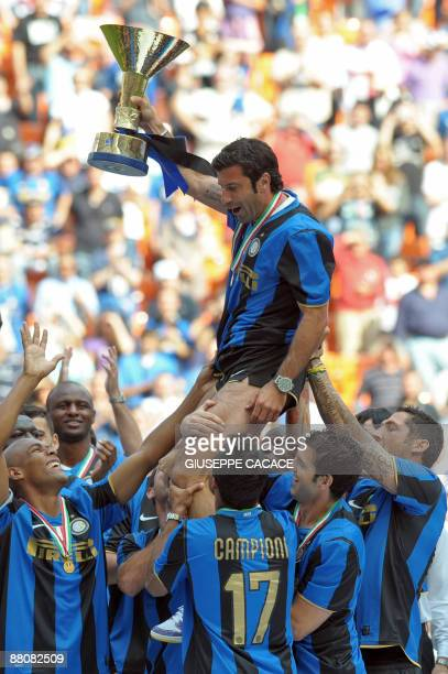 Inter Milan's Portuguese midfielder Luis Figo holds up the trophy as his teammates carry him celebrating the 17th Italian serie A football...