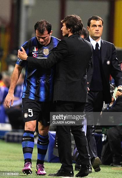 Inter Milan's Serbian midfielder Dejan Stankovic is comforted by Inter Milan's Brazilian coach Leonardo as he leaves the pitch due to an injury...