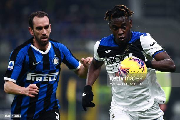 Inter Milan's Uruguayan defender Diego Godin vies with Atalanta's Colombian forward Duvan Zapata during the Italian Serie A football match Inter...