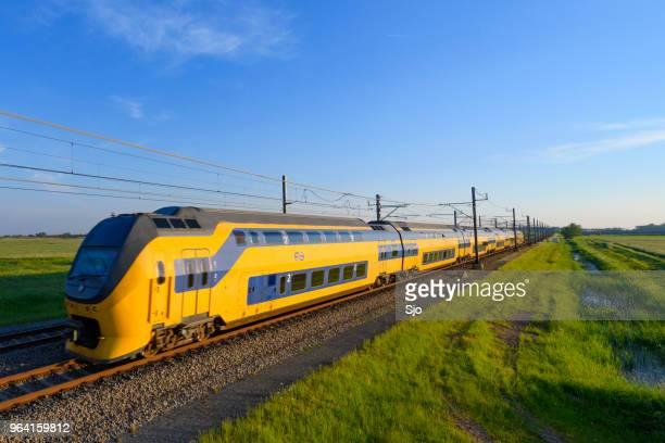 intercity zug der niederländischen eisenbahnen fahren im frühling landschaft - holländische kultur stock-fotos und bilder