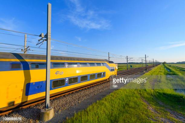 Intercity train of the Dutch Railways NS driving in springtime landscape