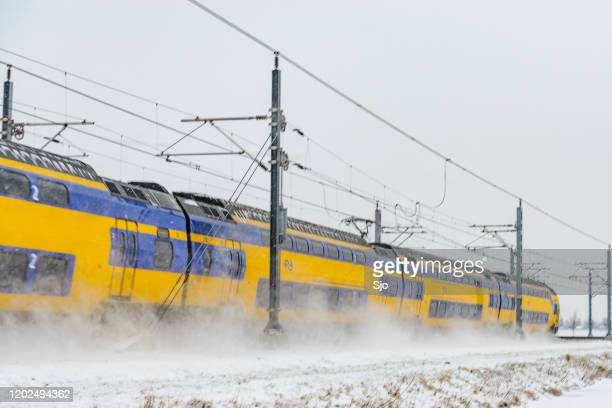 """intercity train of the nederlandse spoorwegen (ns) driving through the snow during a cold winter evening - """"sjoerd van der wal"""" or """"sjo"""" nature stock pictures, royalty-free photos & images"""
