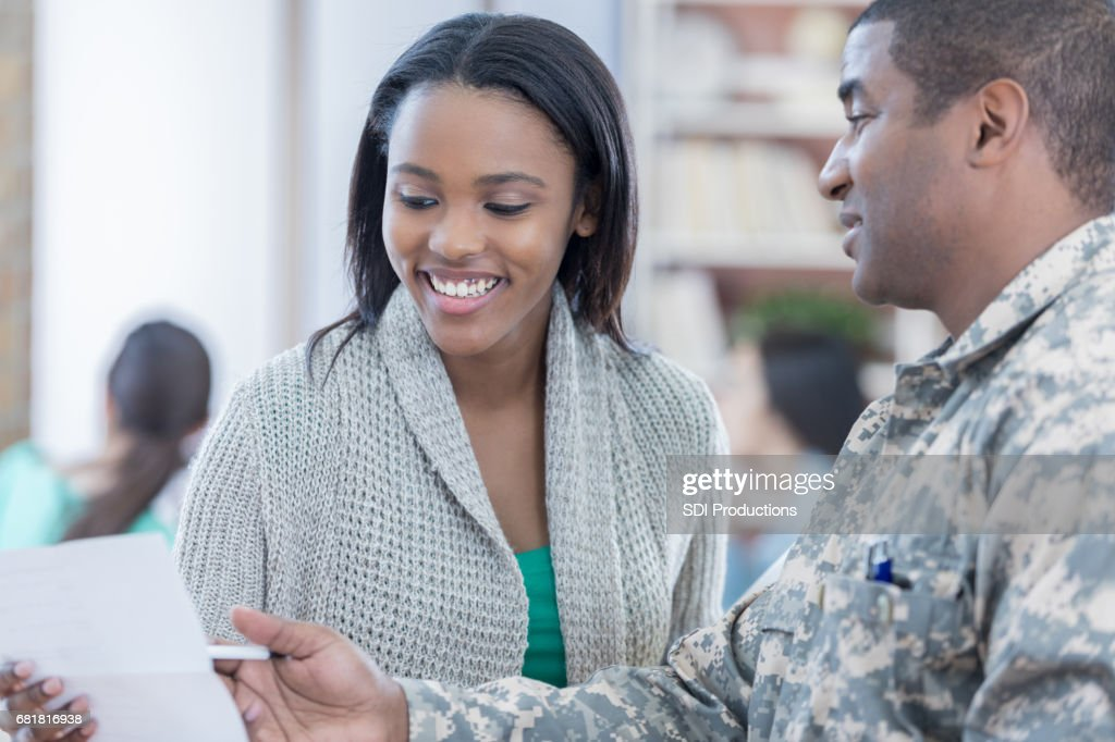 Interested young woman listens to military recruiter : Stock Photo