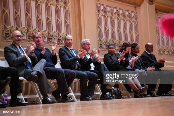 Interfaith leaders and dignitaries seated on stage clapping after a heartfelt performance from the Pittsburgh Symphony In Pittsburgh Pennsylvania...