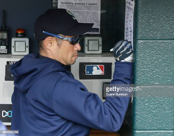 Interim bench coach Ichiro Suzuki of the Seattle Mariners examines their roster during the eighth inning of game one of a doubleheader against the...