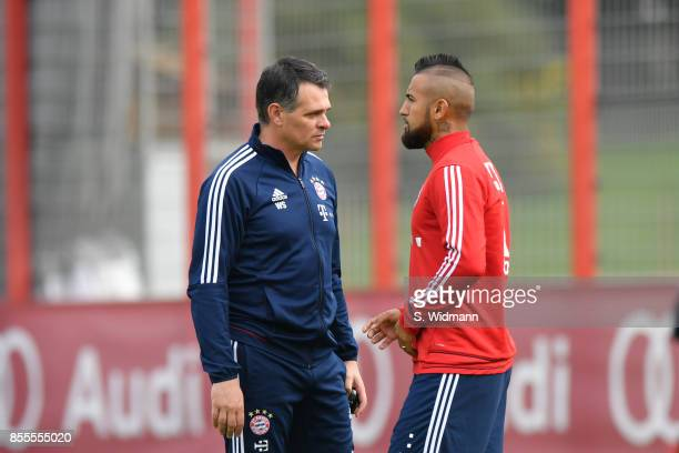 Interim coach Willy Sagnol and Arturo Vidal of FC Bayern Muenchen talk during a training session at Saebener Strasse training ground on September 29...