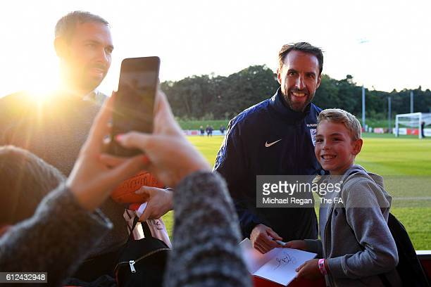 Interim England manager Gareth Southgate poses for photographs with fans after an England training session at St George's Park on October 4, 2016 in...
