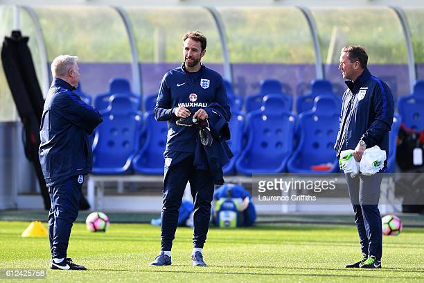 Interim England manager Gareth Southgate speaks with his assistant Sammy Lee and first team coach Steve Steve Holland during an England training...