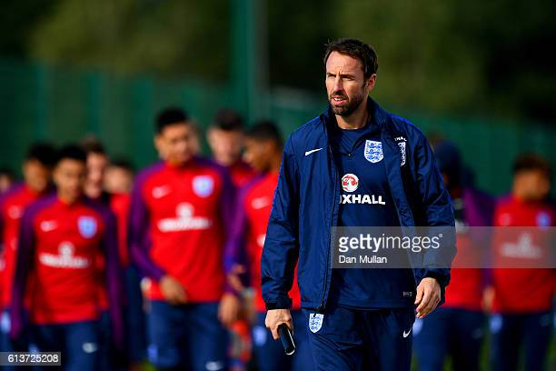 Interim England manager Gareth Southgate walks out with his players for an England training session at the Tottenham Hotspur training ground on...